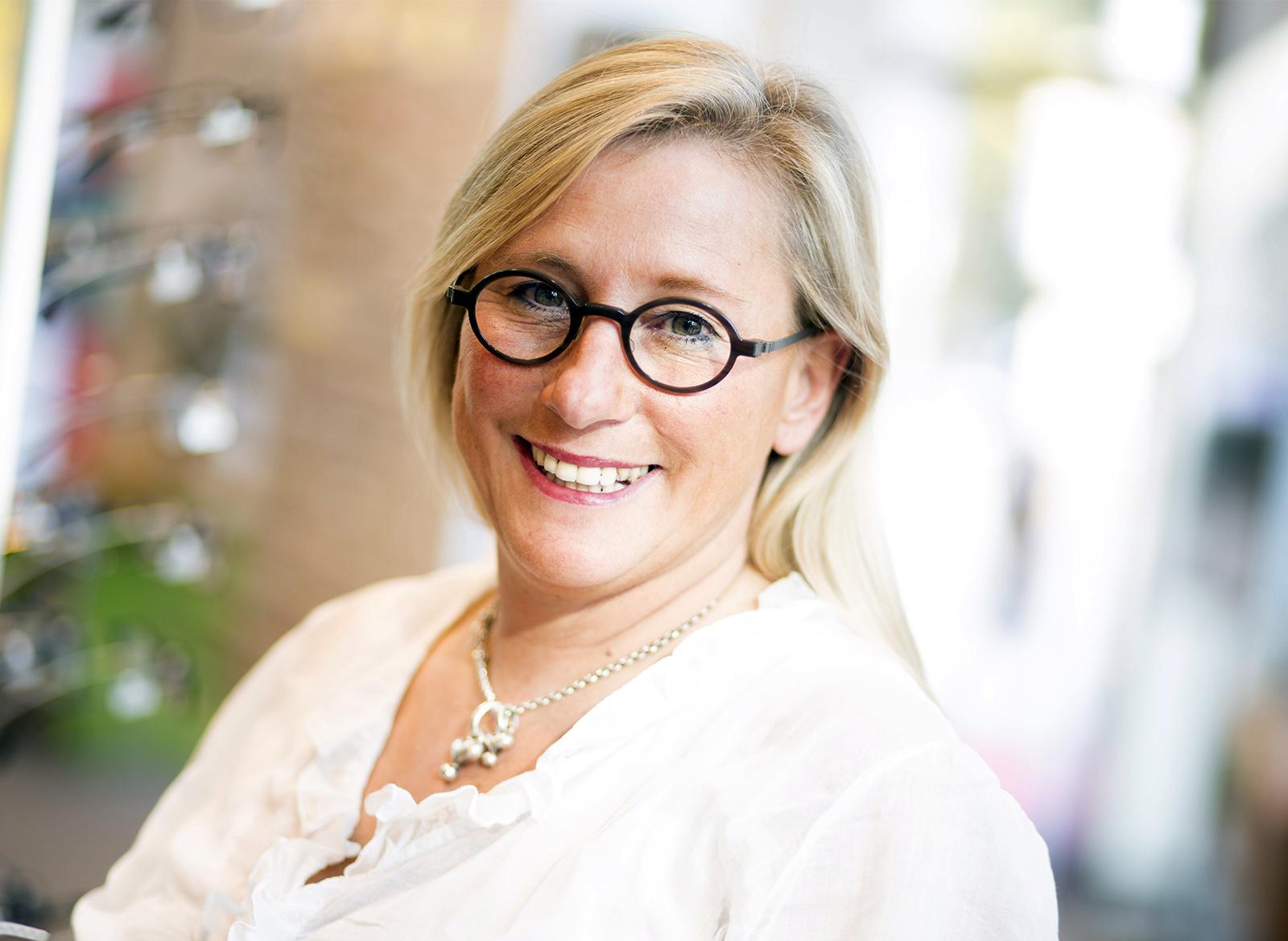Lächelnde Frau mit Brille mit weißen Oberteil.