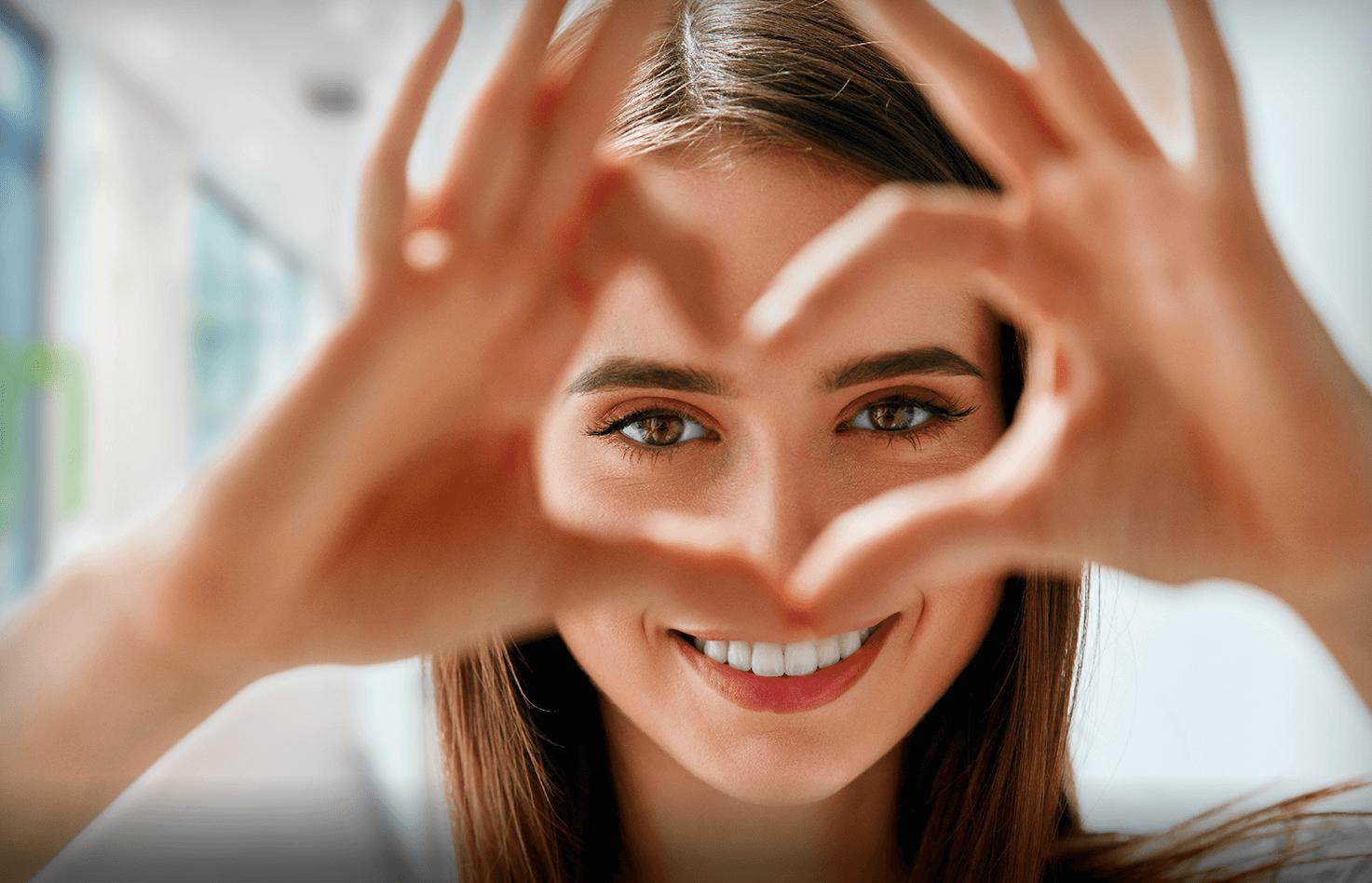 Lächelnde Frau mit Hand die zum Herz geformt sind.