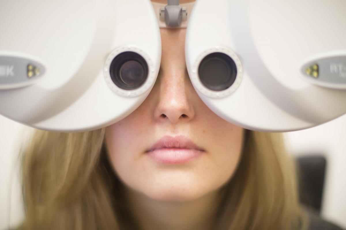 Frau schaut bei Augenprüfung durch Augenmessgerät
