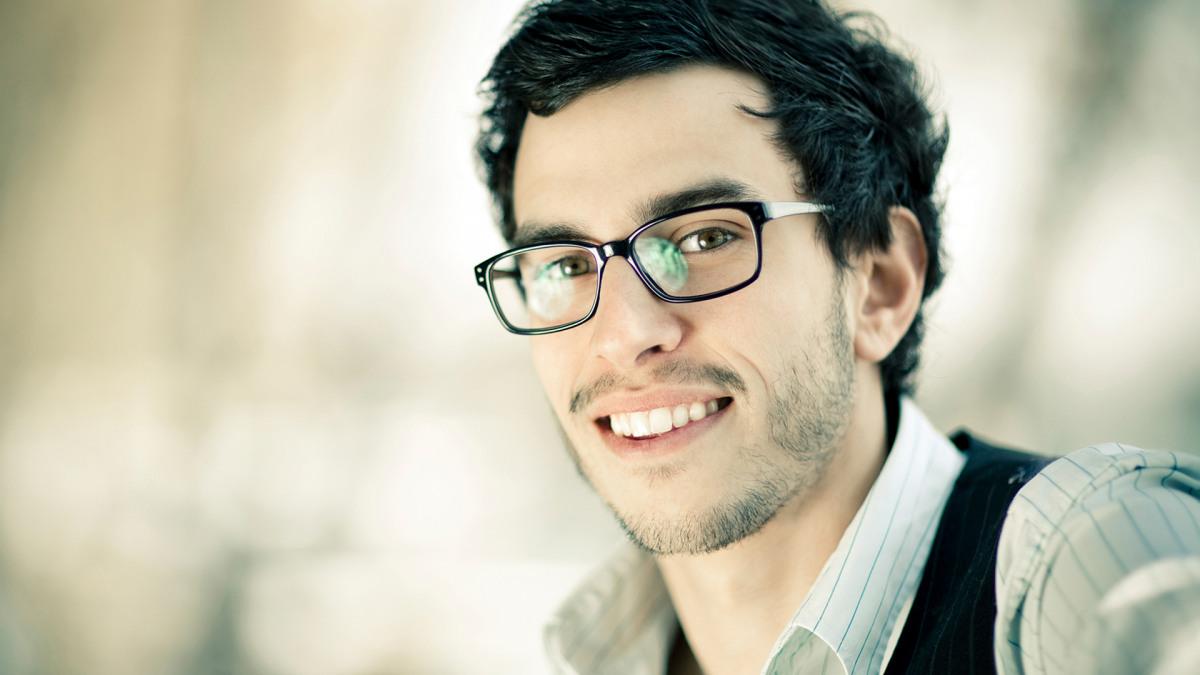 Junger Mann mit dunklen Haaren und Brille.