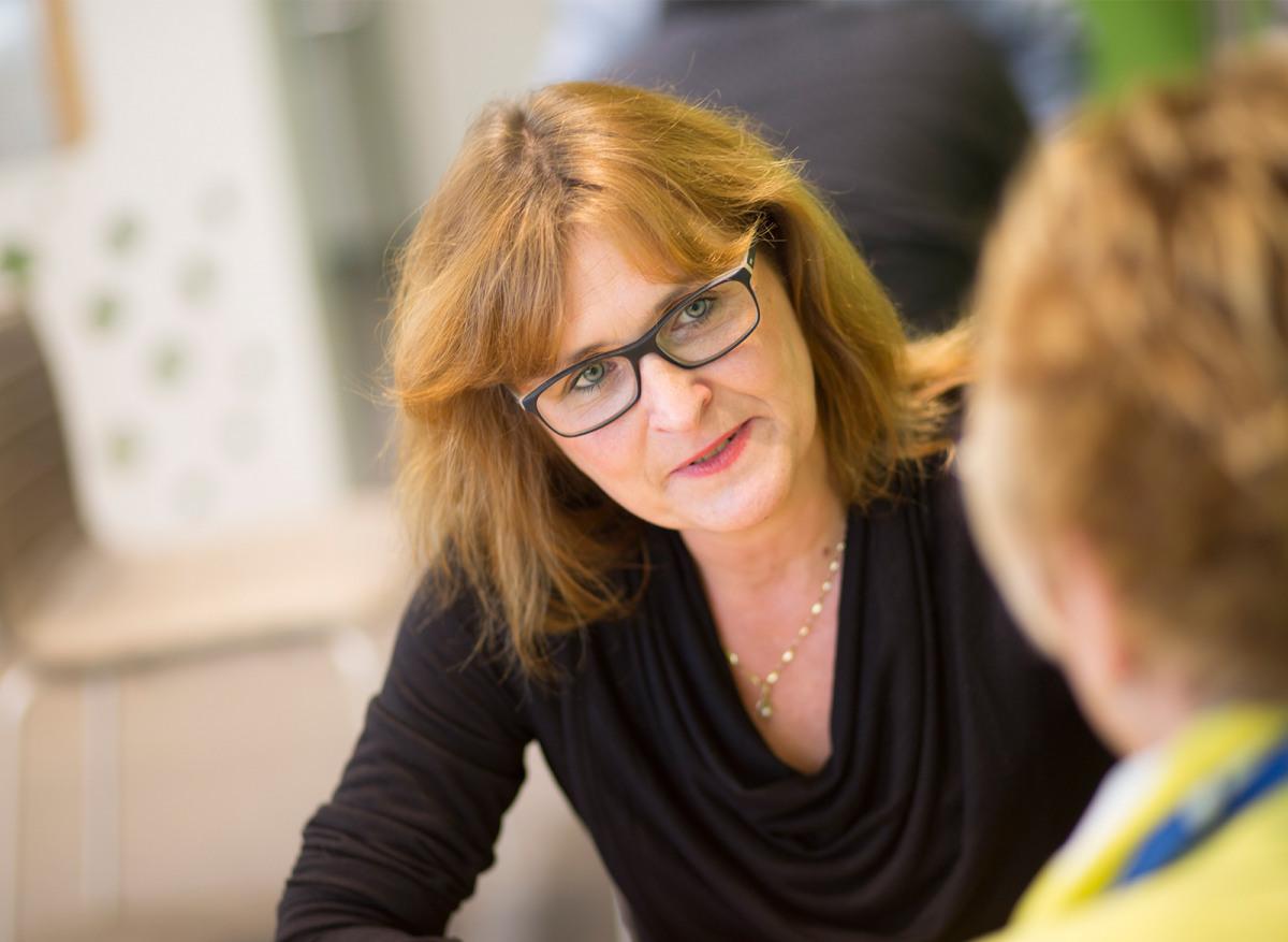 Zuhörende Frau mit Brille mit schwarzem Oberteil.