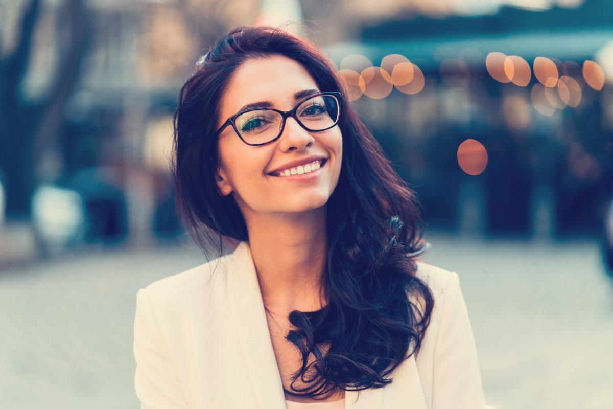 Frau mit dunklen langen Haaren und Brille.