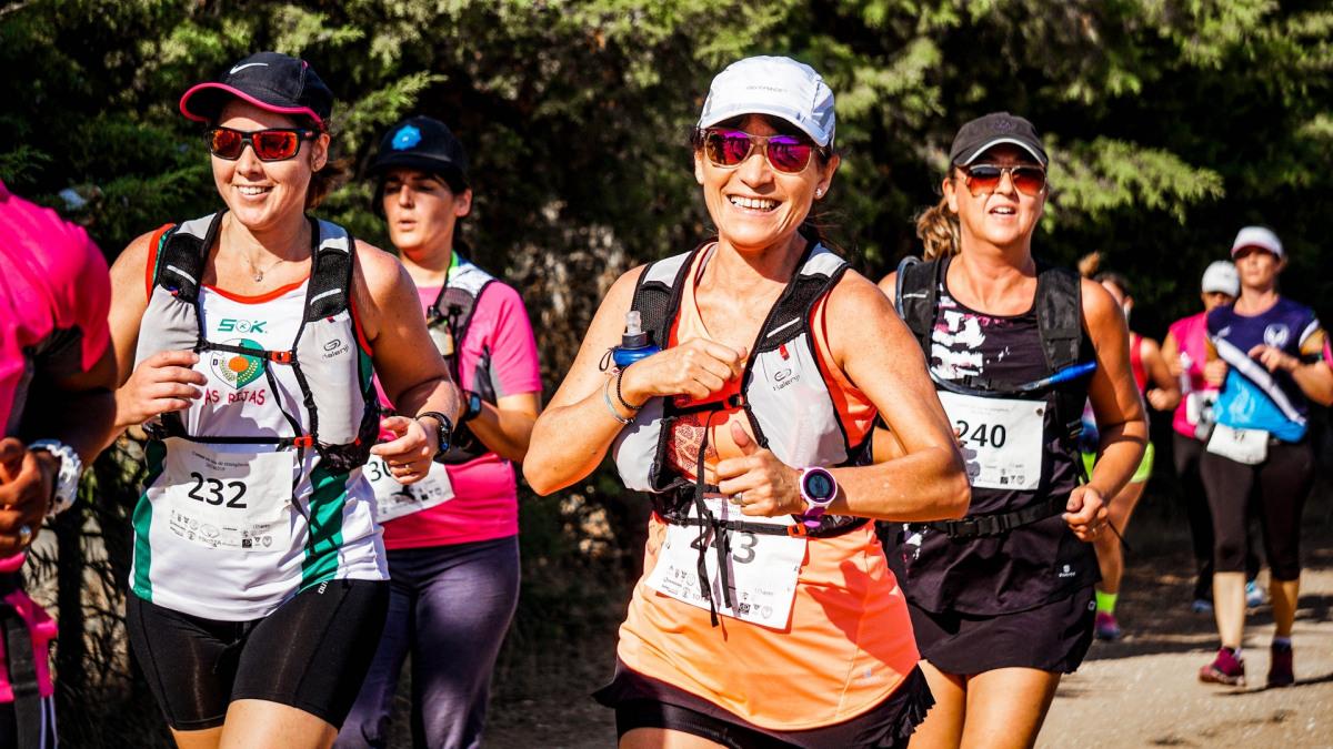 Lächelnde Frauen beim Joggen mit Sonnenbrillen.