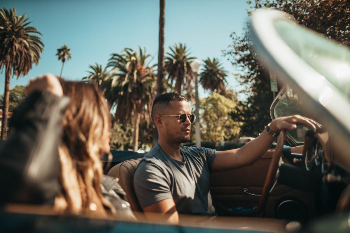 Mann im Auto bei Sonne mit Sonnenbrille.