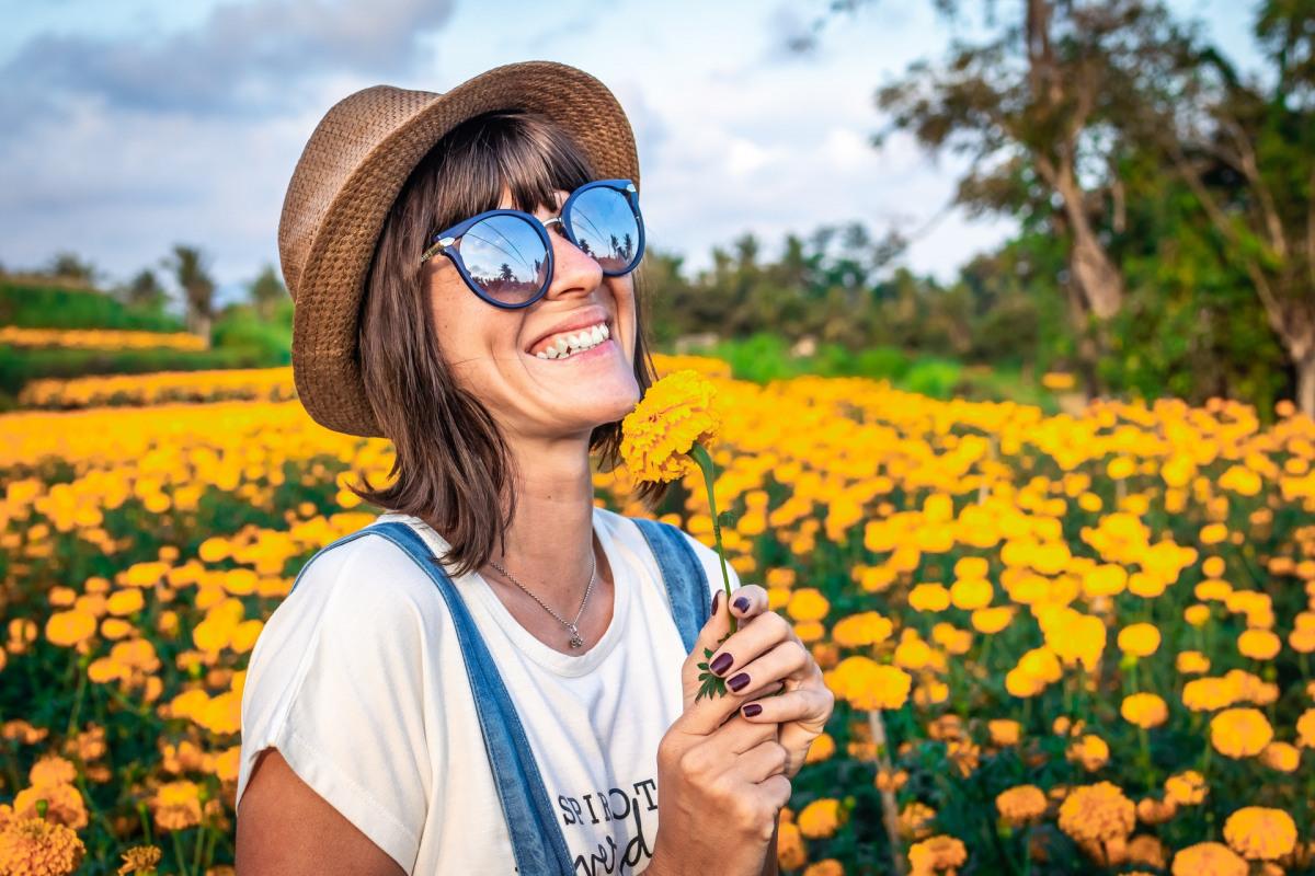 Frau in Blumenfeld am Lächeln mit Sonnenbrille.