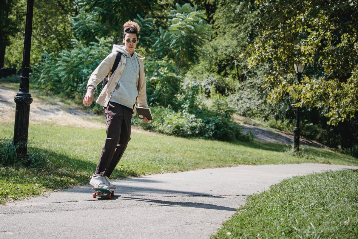 Mann auf Skateboard mit Sonnenbrille.