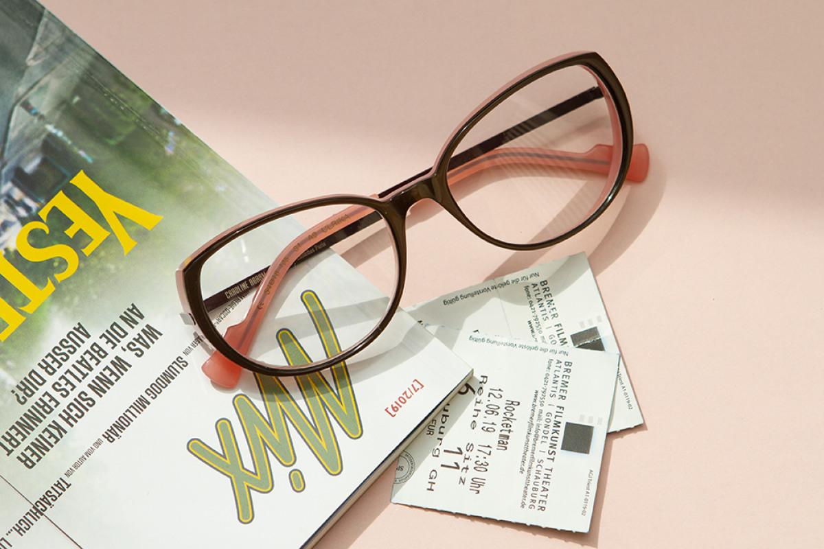 Caroline Abram Brille mit Zeitschrift und zwei Kinokarten auf rosanern Untergrund