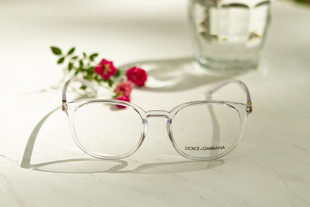 Dolce Gabbana Brille mit Blumen und Wasserkaraffe auf weißen Untergrund.