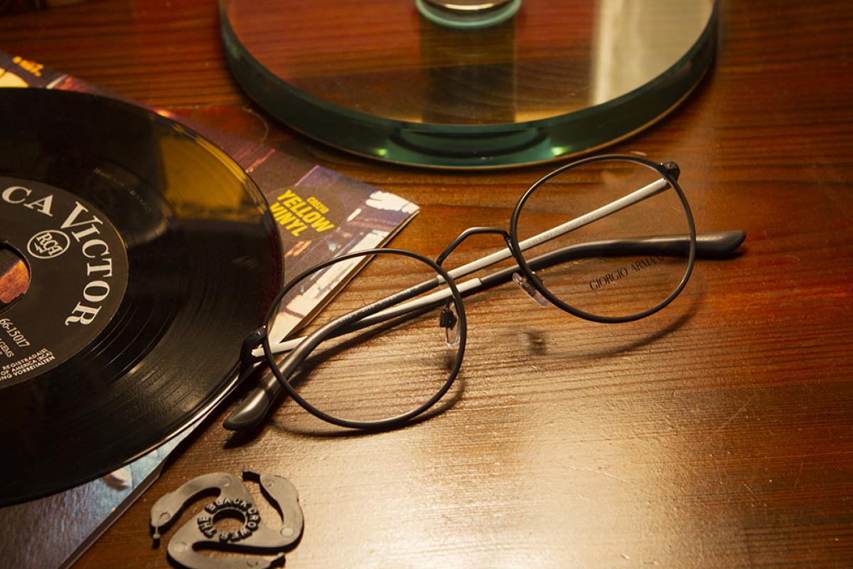 Giorgio Armani Brille neben Schallplatte auf Holztisch.