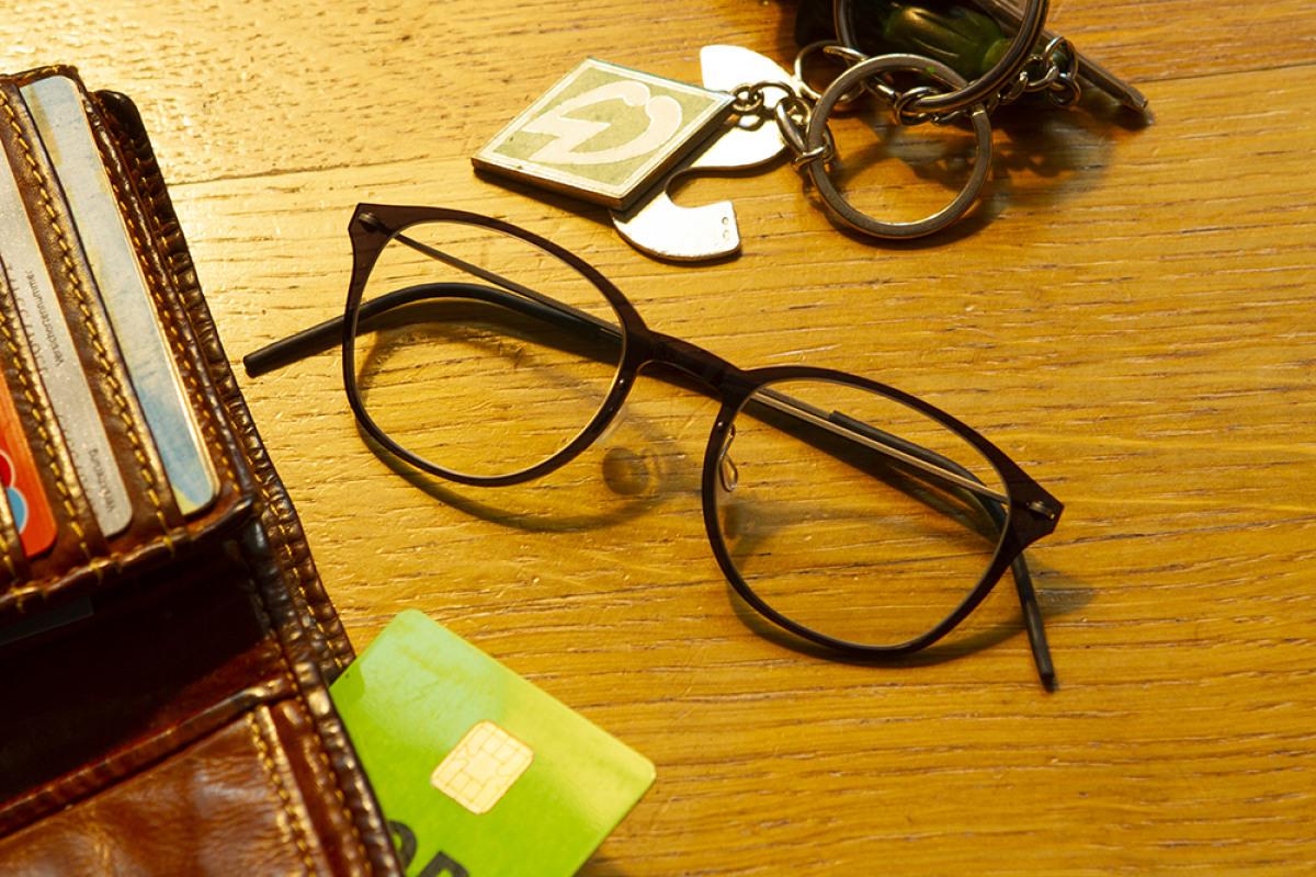 Lindberg Brille neben Portmonee und Schlüssel auf braunen Tisch.