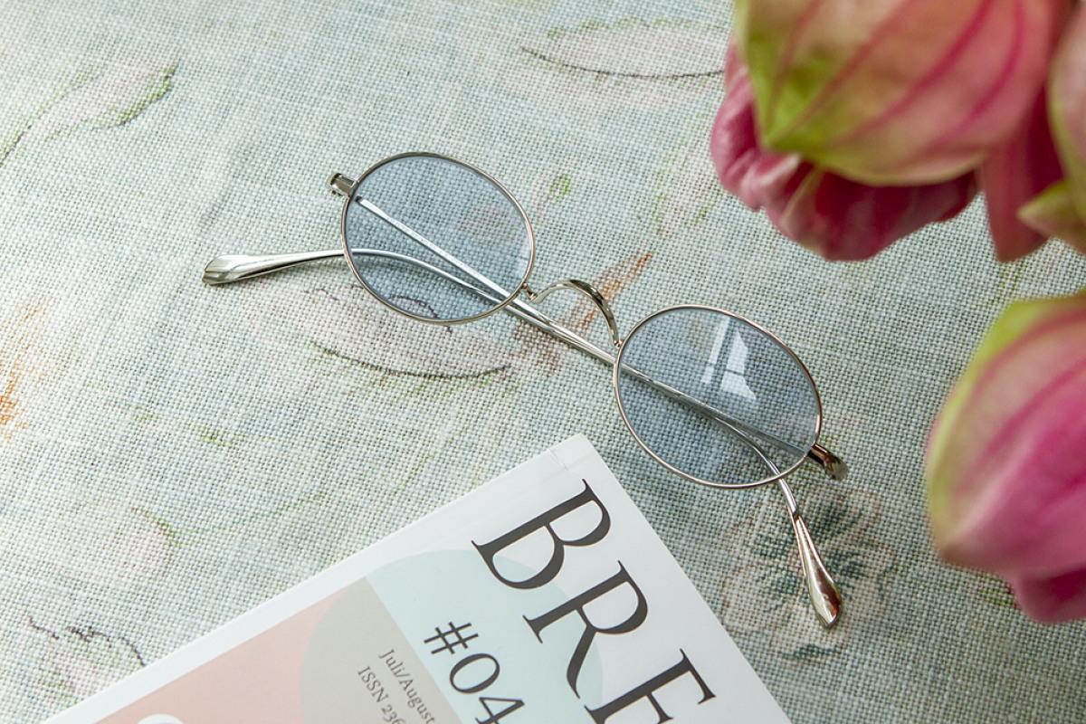 Oliver Peoples Brille neben Zeitschrift mit Blumen auf Tischdecke.