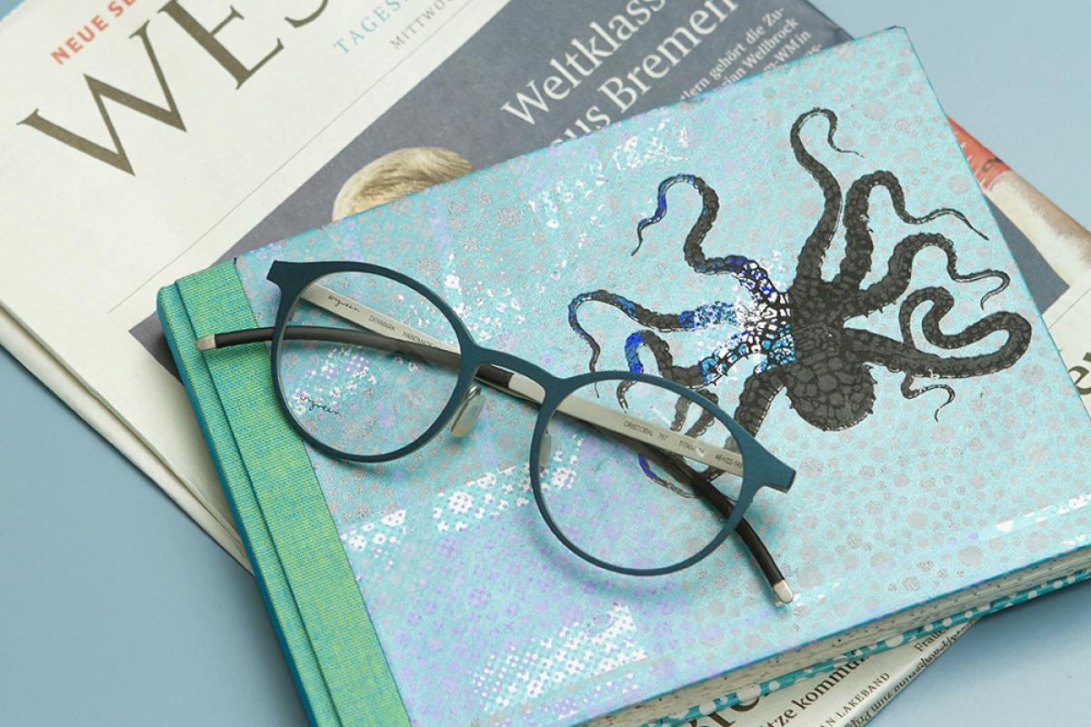 Orgreen Brille auf grün-blauen Buch und Zeitung.