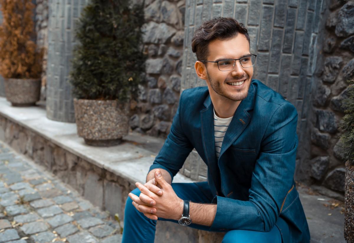 Junger Mann mit blauen Anzug und Brille.
