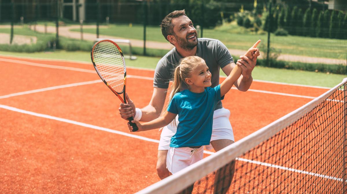 Tennislehrer mit Schülerin auf dem Tennisplatz.