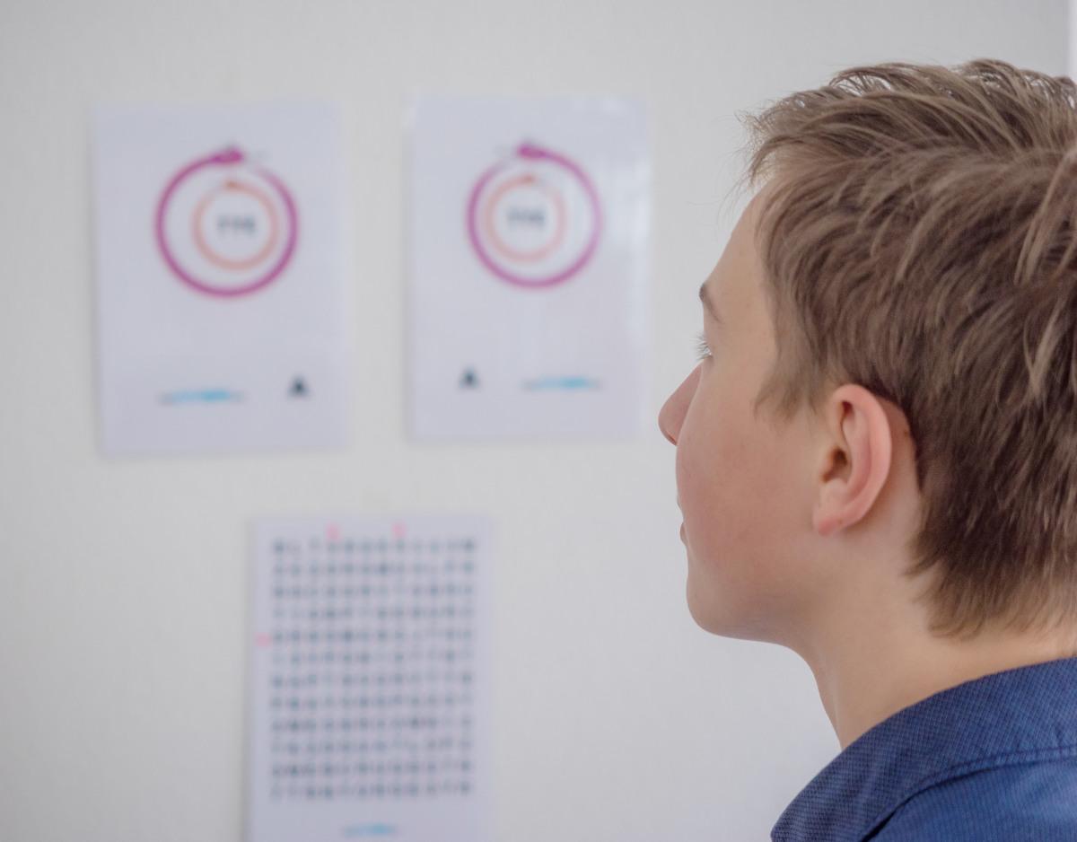 Junge schaut auf verschiedene Augentests.