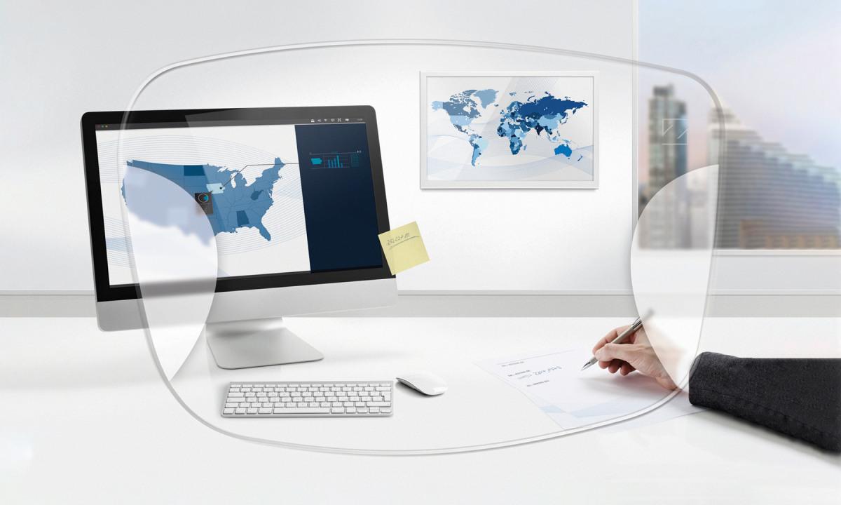 Brillenglas auf Bild vom Computerarbeitsplatz mit Hand die schreibt.